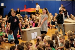 Eager Academy Street Elementary School students help by carrying bins of coin collection boxes filled with coins to benefit Stony Brook Long Island's Children's Hospital.