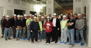 Jenny Tranfaglia, founder of the 'Little Angel Fund,' accepts a check from William Ford of Gilbane Building Company and the Stony Brook University Major Modernization Project construction crews in what will soon be the new state-of-the-art Neonatal Intensive Care Unit (NICU) at Stony Brook University Hospital.