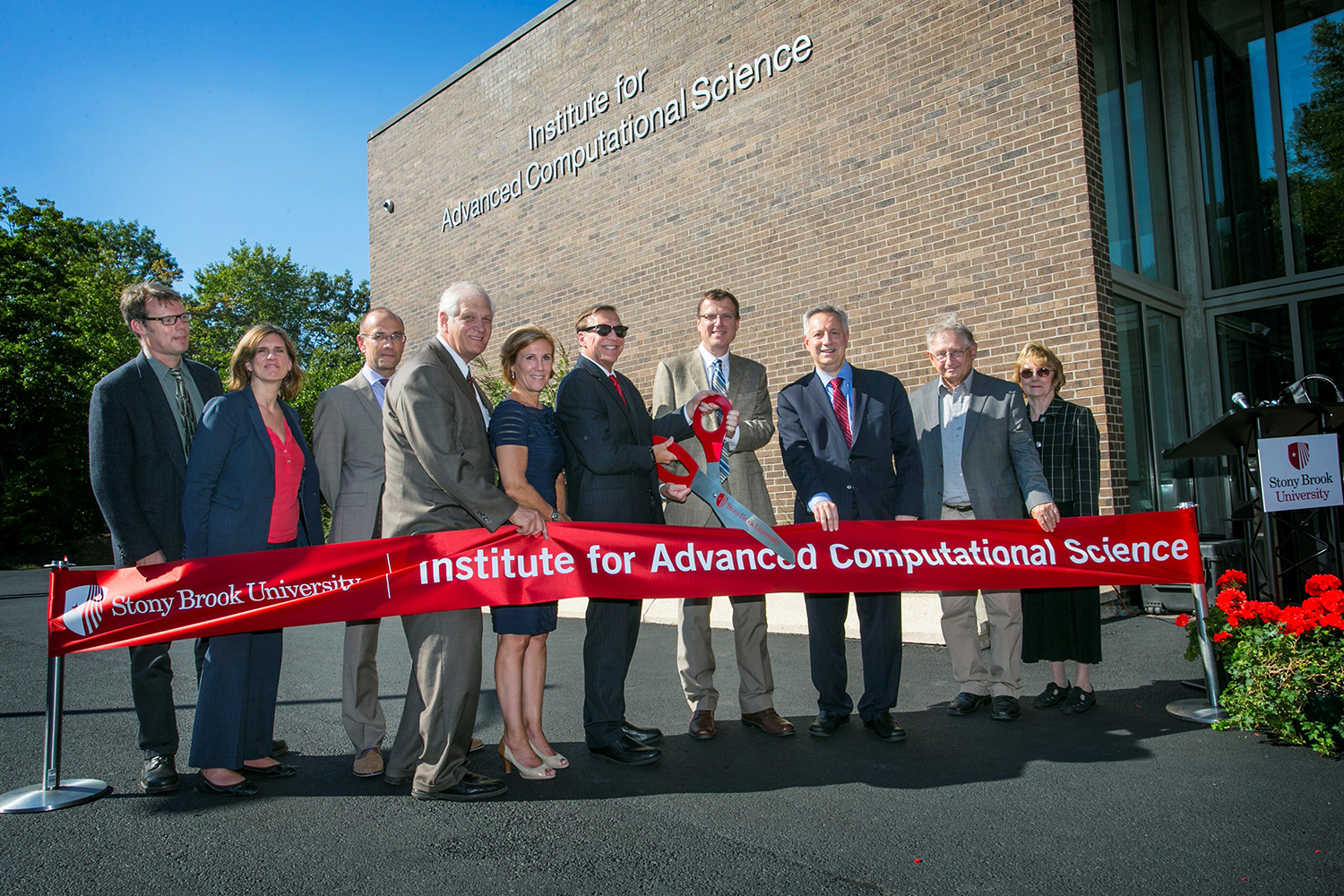 Stony Brook University held a grand opening for the Institute for Advanced Computational Science (IACS). Cutting the ribbon, in center, are Samuel L. Stanley Jr., MD, Stony Brook University President, and Robert Harrison, IACS Director. Also pictured, from left: Alan Calder, Mary Hall, Wolfgang Wander, Steve Englebright, Lynn Allopenna, Dennis Assanis, Peter Paul, and Margaret Wright.