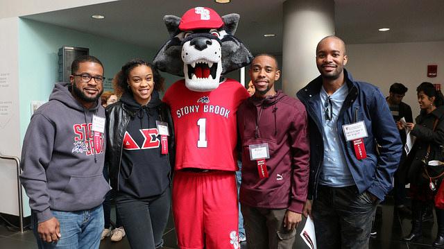 Alumni volunteers meet Wolfie during the Academic Fair on Saturday, April 8, 2017