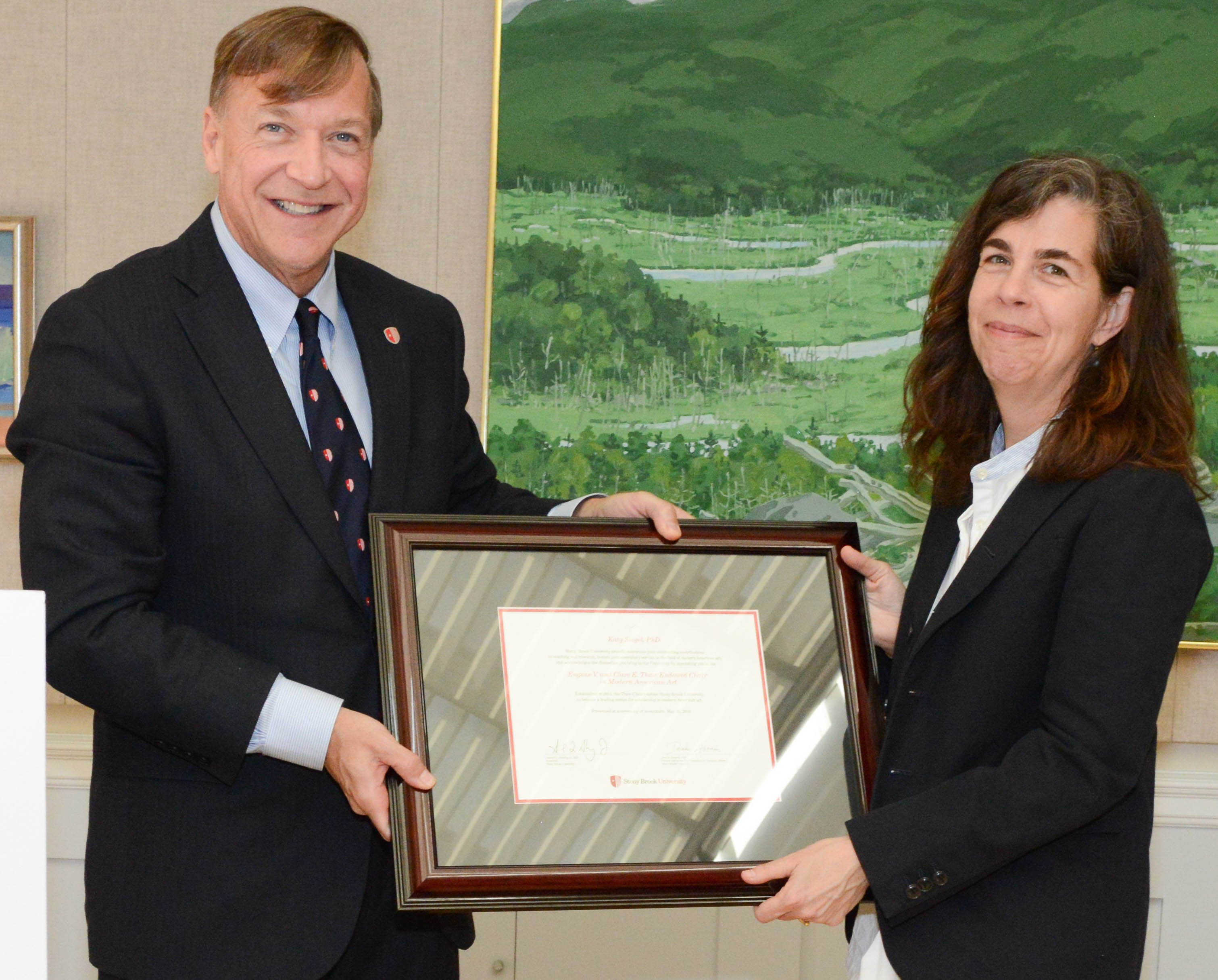 Stony Brook University President Samuel L. Stanley Jr. presents Katy Siegel, PhD, with a declaration honoring her contributions in teaching, research and service to the field of modern American art as she was appointed the inaugural holder of the Eugene V. and Clare E. Thaw Endowed Chair in Modern American Art.