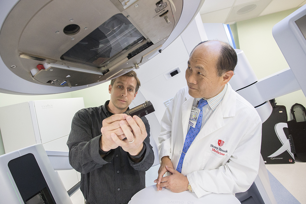 Erik Muller holds one of the diamond monitor devices that could potentially be adapted to newer radiation beam systems that Dr. Samuel Ryu has incorporated into treatment protocols at Stony Brook University Cancer Center.