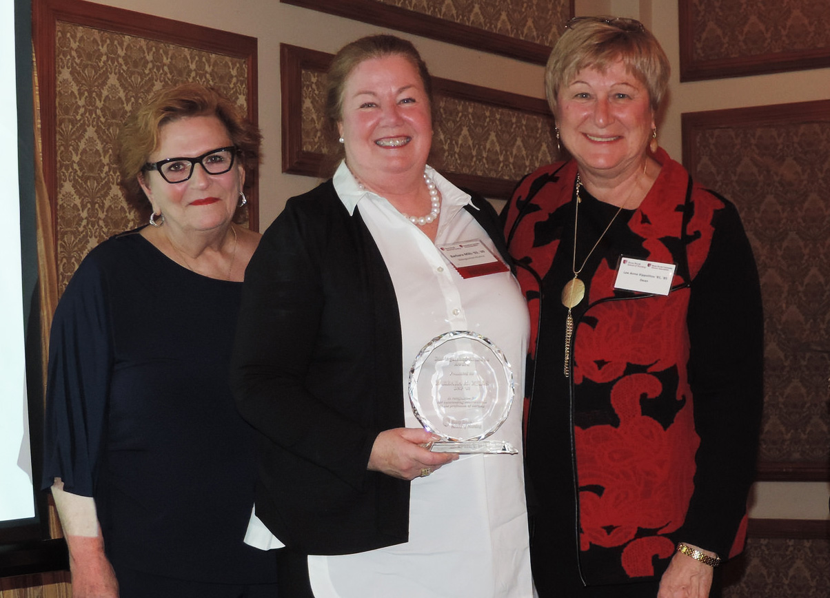 Distinguished Alumna Dr. Barbara Mills '09 (center) receives her award from Patricia Jacobowitz BS '79, MS '86, DNP '09, President of the School of Nursing Alumni Board, and Lee Anne Xippolitos, Dean of the School of Nursing