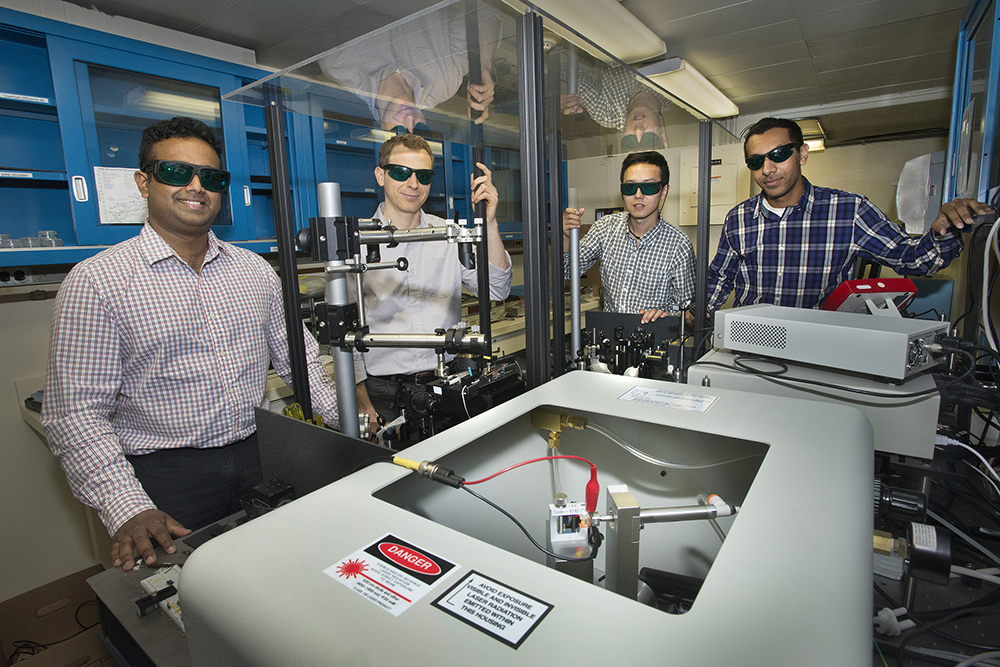 Lead author Matthew Eisaman, center, in a laser lab at Brookhaven Lab with co-authors, from left: Nanditha Dissanayake, and Yutong Pang and Ahsan Ashraf (both PhD students in Physics at Stony Brook University).