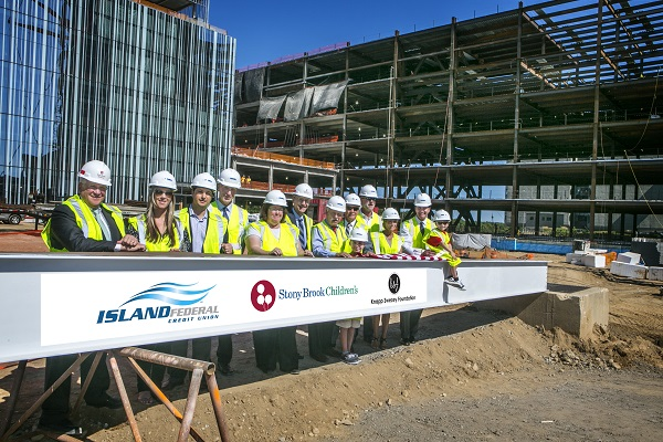 The installation of the final beam for the new Stony Brook Children's Hospital was celebrated at a 'topping off' ceremony attended by Stony Brook Medicine leaders Kenneth Kaushansky, MD, L. Reuven Pasternak, MD and Margaret McGovern, MD, PhD; Knapp Swezey Foundation representatives Danielle Knapp-SanGiovanni and Jesse SanGiovanni, Dave and Michele Knapp, and Foundation board member John J. Roe, III; Island Federal Credit Union CEO Bret Sears; as well as elected officials, donors, Stony Brook Children's patients and family members. The beam was signed by them and others instrumental in supporting the construction of the new building. Credit: Stony Brook Medicine.