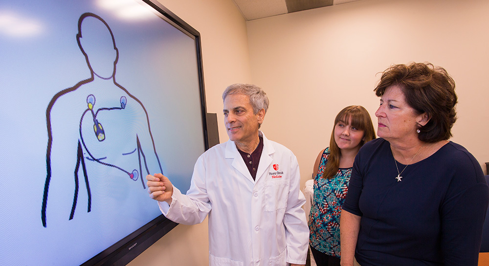 Dr. Fred Friedberg explains the heart monitor and electrode placement used in the chronic fatigue syndrome study to fellow investigator Dr. Patricia Bruckenthal of the School of Nursing, and Jenna Adamowicz, center, study coordinator from the Department Psychiatry.