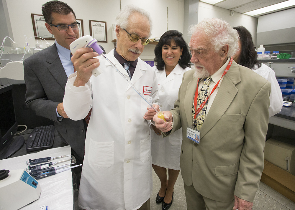 Dr. Lorne Golub, left, and Dr. Francis Johnson, inventors of the compounds to treat inflammation, manipulate the lead compound that will be evaluated by Traverse Biosciences. Also pictured are Joseph Scaduto of Traverse Biosciences and Dr. Maria Ryan of the School of Dental Medicine.