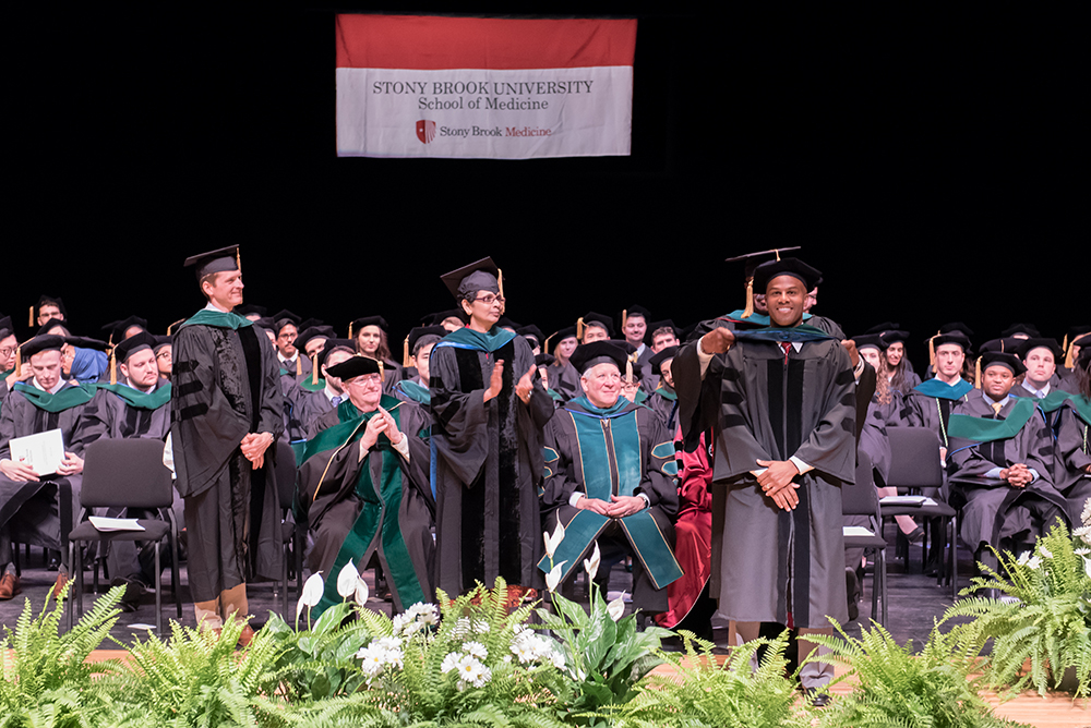 Marshall Leonard, far right, one of the 124 graduates who received MD degrees during the traditional Doctoral Hooding Ceremony. Dr. Leonard's father, Tommy Leonard Jr., MD, took the honor in hooding his son.