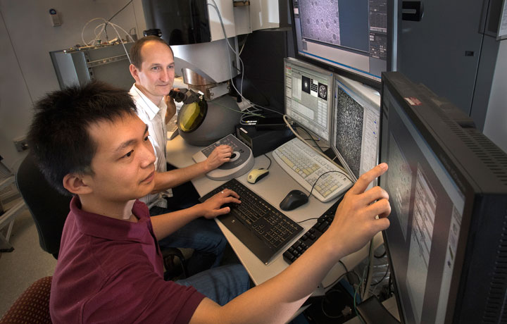 Stony Brook University graduate student Qiyuan Wu and Brookhaven Lab Center for Functional Nanomaterials (CFN) staff scientist Dmitri Zakharov studying samples at the Titan Environmental Transmission Electron Microscope at the CFN.