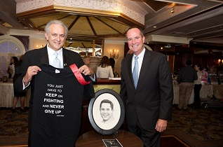 Mike DeMartis, left, stands with Gary Bie, Chief Financial Officer of Stony Brook University Hospital, and a photo of DeMartis's late son, Mickey. Bie suggested DeMartis honor his son's life by naming a room in his honor at the planned new Stony Brook Children's Hospital. The family raised more than $50,000 at an Oct. 10 dinner event, which will be matched by an anonymous donor for a total impact of more than $100,000.