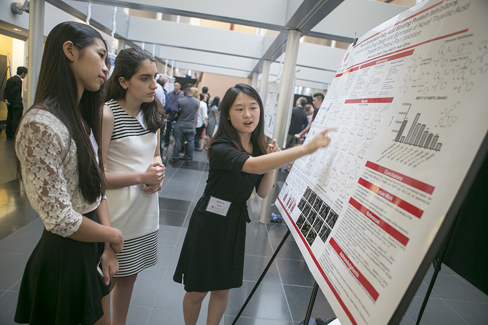 Simons Summer Research Fellow Sarah Lee of Syosset High School, one of 17 Siemens Competition in Math, Science & Technology regional finalists mentored at Stony Brook University, explains her research during a poster session in the Wang Center at Stony Brook University on August 11.