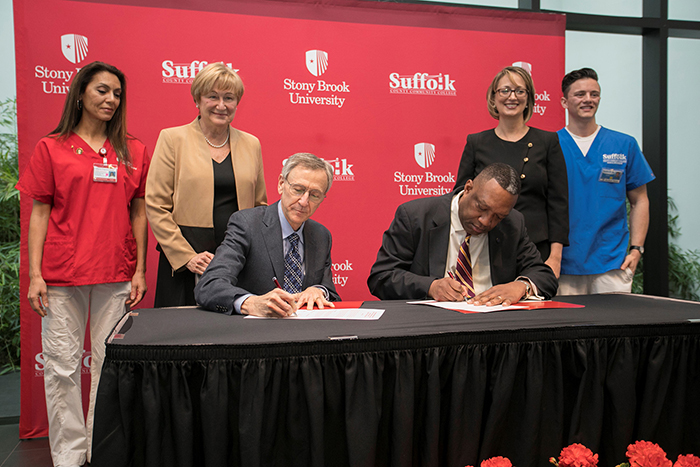 Kenneth Kaushansky, MD, MACP, Senior Vice President of the Health Sciences and Dean of the Stony Brook University School of Medicine (front, left); and Dr. Shaun L. McKay, President, Suffolk County Community College (front, right); sign a memorandum of understanding to officially launch the Suffolk-Stony Brook Nursing First Program. Also pictured, from left: Stony Brook nursing student Catherine Grigorians-Manzo; Dr. Lee Anne Xippolitos, Dean of Stony Brook University School of Nursing; Dr. Cheryl Shaffer, Associate Dean, Suffolk County Community College School of Nursing; and Suffolk nursing student Scott Schultz.