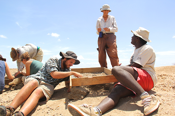 Meave Leakey discusses fossil sieving practices with TBI Origins Field School students in Kenya. Photo credit Mike Hettwer.