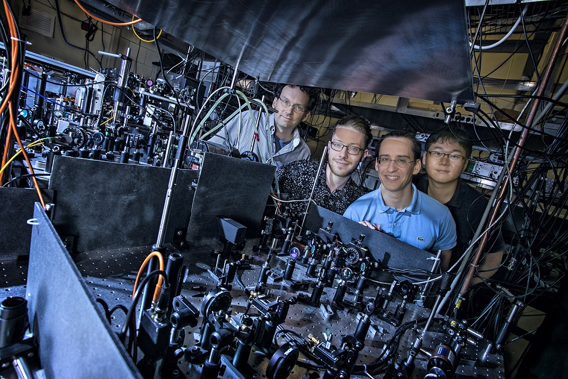 Professor Schneble, far left, with PhD students Michael Stewart, Ludwig Krinner, and Joonhyuk Kwon, assemble around the large atom trap system created in their Stony Brook lab.