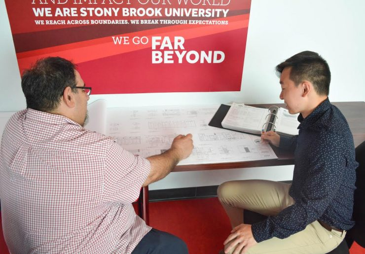 William Zhu '21 reviewing architectural plans with Jeffrey Moss, FSA Facilities Manager.
