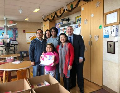 Sophia Espiritu (center) surrounded by her family and Tamarac Elementary School principal, Michael Saidens, as she donates hundreds of ComfyChemo shirts.