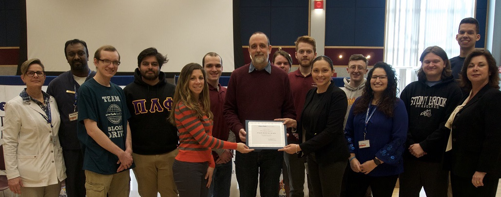 New York Blood Center professional staff present award to Daria Carioscia and Paul Newland of the Staller Center with student members of the Student Blood Drive Committee