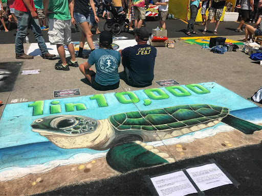 Pictured in their Tidal Tees shirts, Sydney Bell and her father, Brian Bell, with their sidewalk chalk art of a sea turtle hatchling raising awareness for the various threats to sea turtles.