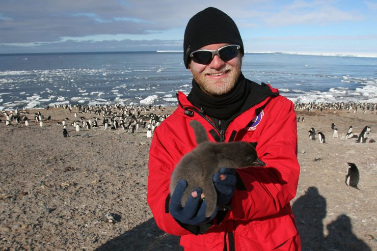 Noah Strycker with an adelie penguin chick