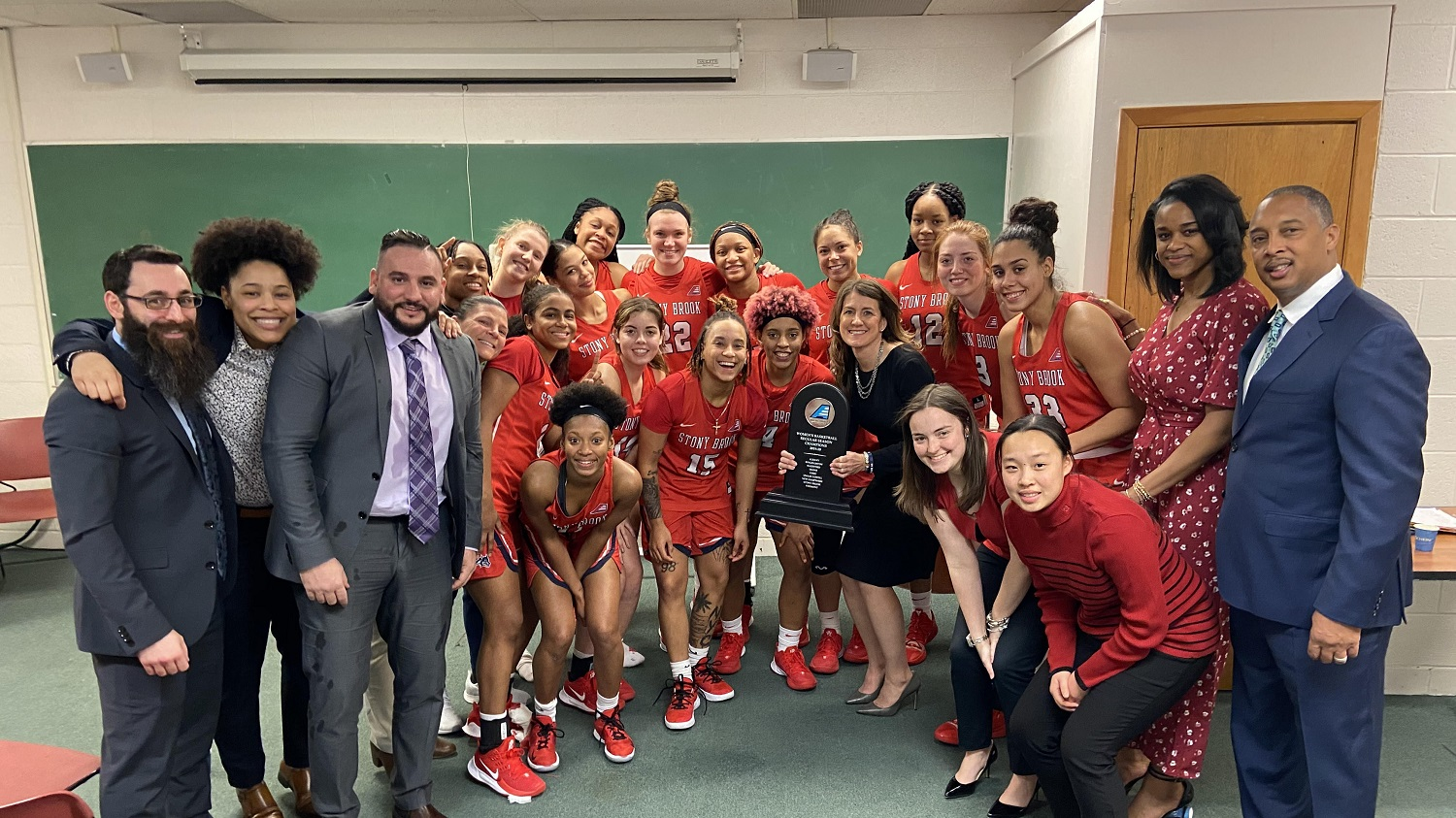 Coach Caroline McCombs and team display the America East regular-season championship trophy after February 19 win at Vermont.