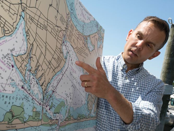 Chris Gobler points to an area hit by brown tide, a threat to Long Island's ecosystems that SoMAS researchers are striving to defeat.