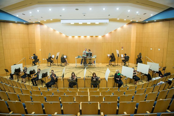 Sixteen violinists participating in the networking experiment in which they are connected to a computer system hearing only the sound received from the computer. Photo by Chen Damari
