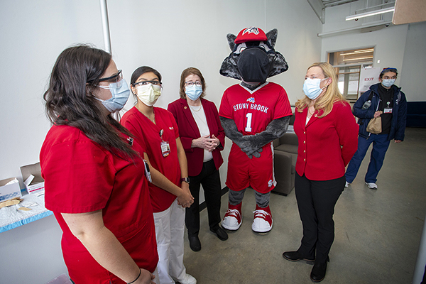 Dr. Maurie McInnis, President Of Stony Brook University, Wolfie and Dr. Margaret McGovern, Stony Brook Medicine Vice President for Health System Clinical Programs and Strategy, thank healthcare workers who are giving their time to help vaccinate Long Island.