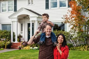 Photo of a happy family in front of their home.