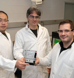 """Professor Peter Khalifah (middle) with graduate students Zhuo Li (left) and Gerard Mattei (right) holding a """"pouch cell"""" battery attached to a frame used for synchrotron x-ray studies (Note: This photo was taken prior to current COVID-19 social distancing guidelines). Courtesy of Brookhaven Laboratory"""