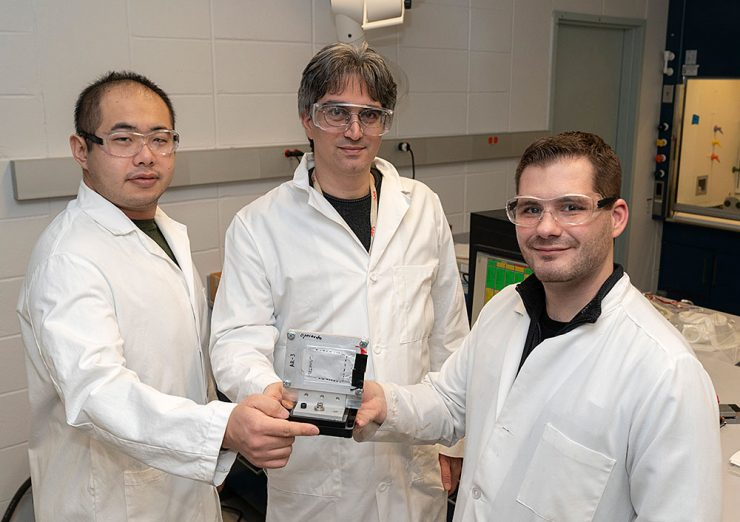 "Professor Peter Khalifah (middle) with graduate students Zhuo Li (left) and Gerard Mattei (right) holding a ""pouch cell"" battery attached to a frame used for synchrotron x-ray studies (Note: This photo was taken prior to current COVID-19 social distancing guidelines). Courtesy of Brookhaven Laboratory"