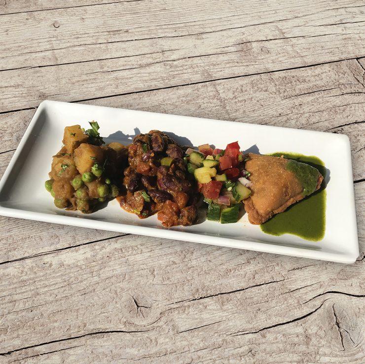 Tadka, Essence of India vegetable plate with rajma red bean stew, aloo matar (potato and pea stew), vegetable samosa, cucumber salad, hari green cilantro chutney.
